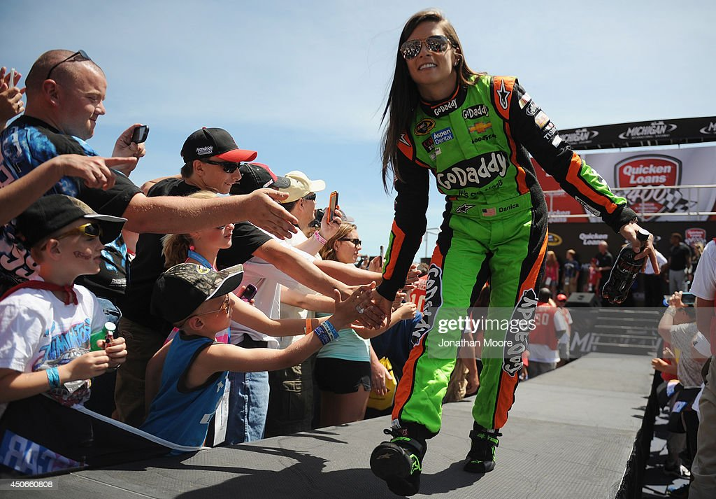 Danica Patrick, driver of the #10 GoDaddy Chevrolet, shakes hands with fans after being introduced during pre-race introductions for the NASCAR Sprint Cup Series Quicken Loans 400 at Michigan International Speedway on June 15, 2014 in Brooklyn, Michigan.