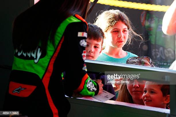 Danica Patrick driver of the GoDaddy Chevrolet signs autographs in the garage area during practice for the NASCAR Sprint Cup Series Sprint Unlimited...