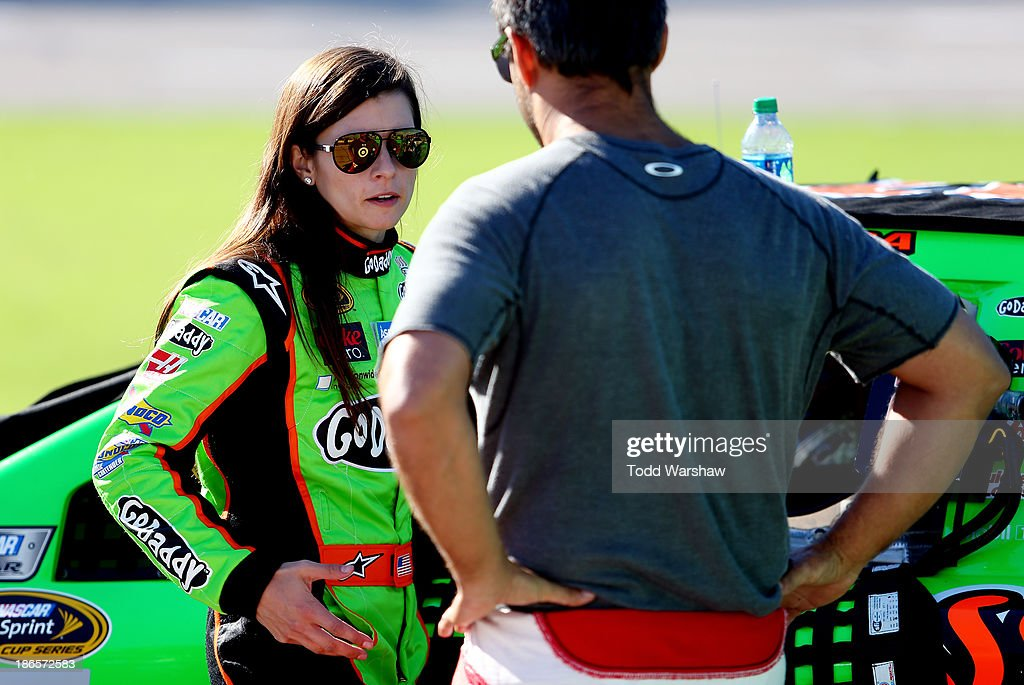 Danica Patrick, driver of the #10 GoDaddy Chevrolet, speaks with Juan Pablo Montoya, driver of the #42 Target Chevrolet, on the grid during qualifying for the NASCAR Sprint Cup Series AAA Texas 500 at Texas Motor Speedway on November 1, 2013 in Fort Worth, Texas.