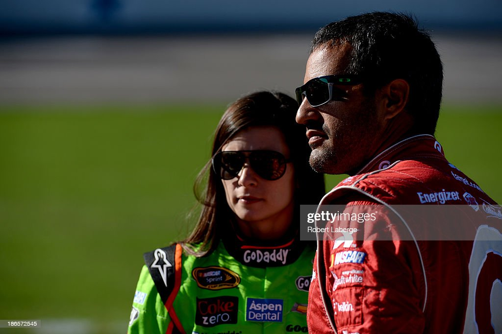 Danica Patrick, driver of the #10 GoDaddy Chevrolet, talks with Juan Pablo Montoya, driver of the #42 Target Chevrolet, on the grid during qualifying for the NASCAR Sprint Cup Series AAA Texas 500 at Texas Motor Speedway on November 1, 2013 in Fort Worth, Texas.