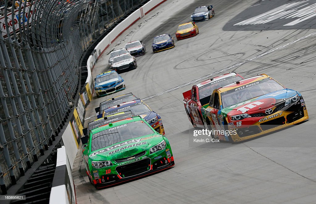 Danica Patrick, driver of the #10 GoDaddy.com Chevrolet, and Kyle Busch, driver of the #18 M&M's Toyota, lead a pack of cars into turn one during the NASCAR Sprint Cup Series Food City 500 at Bristol Motor Speedway on March 17, 2013 in Bristol, Tennessee.