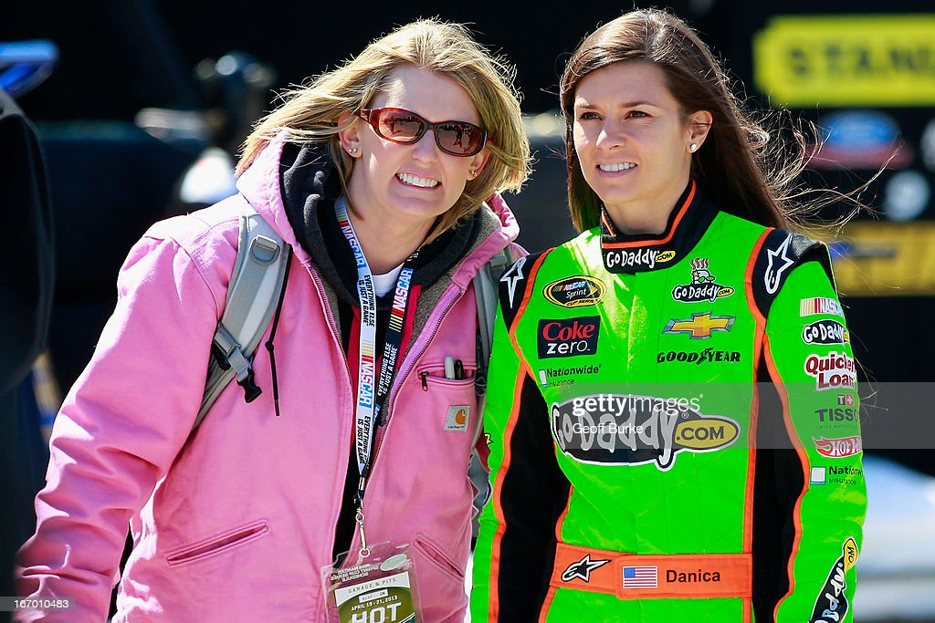 Danica Patrick (r), driver of the #10 GoDaddy.com Chevrolet, poses for a picture with a fan in the garage prior to practice for the NASCAR Sprint Cup Series STP 400 at Kansas Speedway on April 19, 2013 in Kansas City, Kansas.
