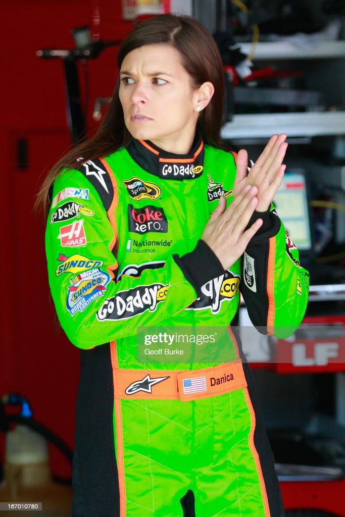 Danica Patrick, driver of the #10 GoDaddy.com Chevrolet, stands in the garage prior to practice for the NASCAR Sprint Cup Series STP 400 at Kansas Speedway on April 19, 2013 in Kansas City, Kansas.