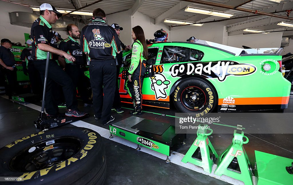 Danica Patrick (R), driver of the #10 GoDaddy.com Chevrolet, talks with crew members in the garage during practice for the NASCAR Sprint Cup Series Daytona 500 at Daytona International Speedway on February 20, 2013 in Daytona Beach, Florida.