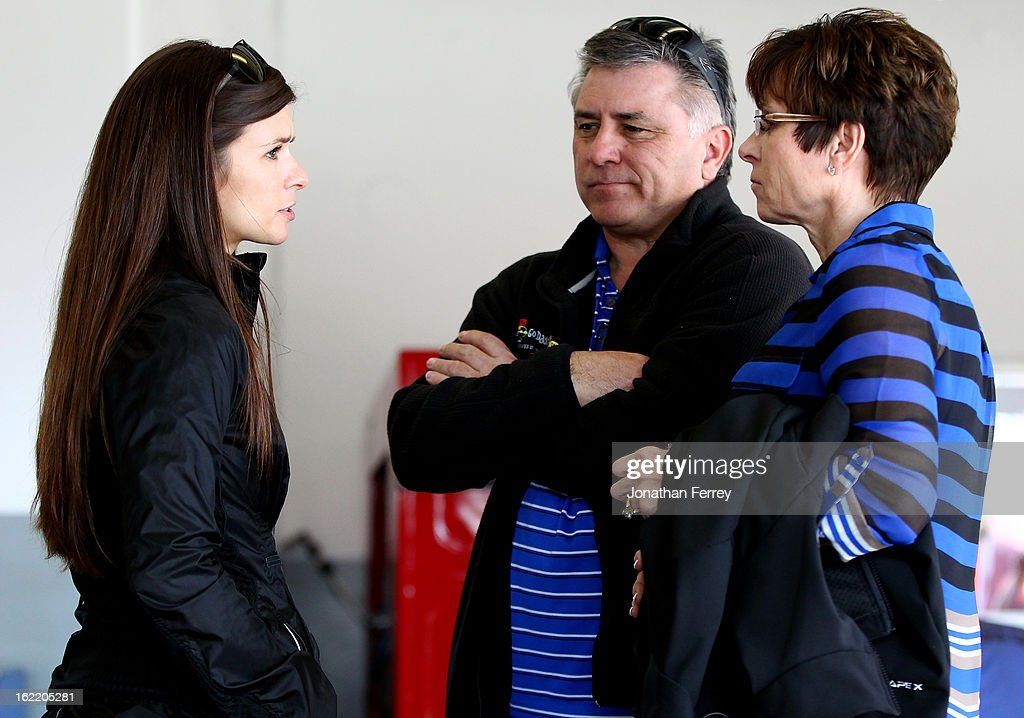 Danica Patrick (L), driver of the #10 GoDaddy.com Chevrolet, talks with her parents T.J. (C) and Bev (R) in the garage during practice for the NASCAR Sprint Cup Series Daytona 500 at Daytona International Speedway on February 20, 2013 in Daytona Beach, Florida.