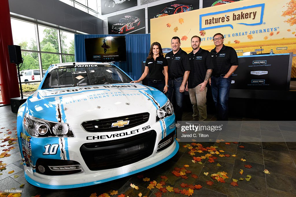 Danica Patrick, driver of the #10 Stewart-Haas Racing Chevrolet, Tony Stewart, co-owner of Stewart-Haas Racing, Sam Marson and Dave Marson, founders of Nature's Bakery, pose for a photo opportunity after announcing a multiyear deal partnership during a press conference on August 18, 2015 in Kannapolis, North Carolina. The partnership will begin with the 2016 NASCAR Sprint Cup Series season.