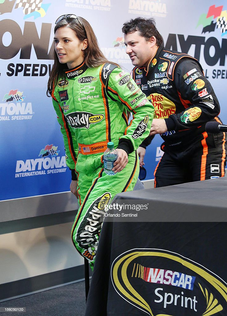 Danica Patrick, left, and Tony Stewart hurry off the podium stage following a press conference as the two head toward afternoon testing during NASCAR Sprint Cup Series Preseason Thunder at Daytona International Speedway in Daytona Beach, Florida, Thursday, January 10, 2013.