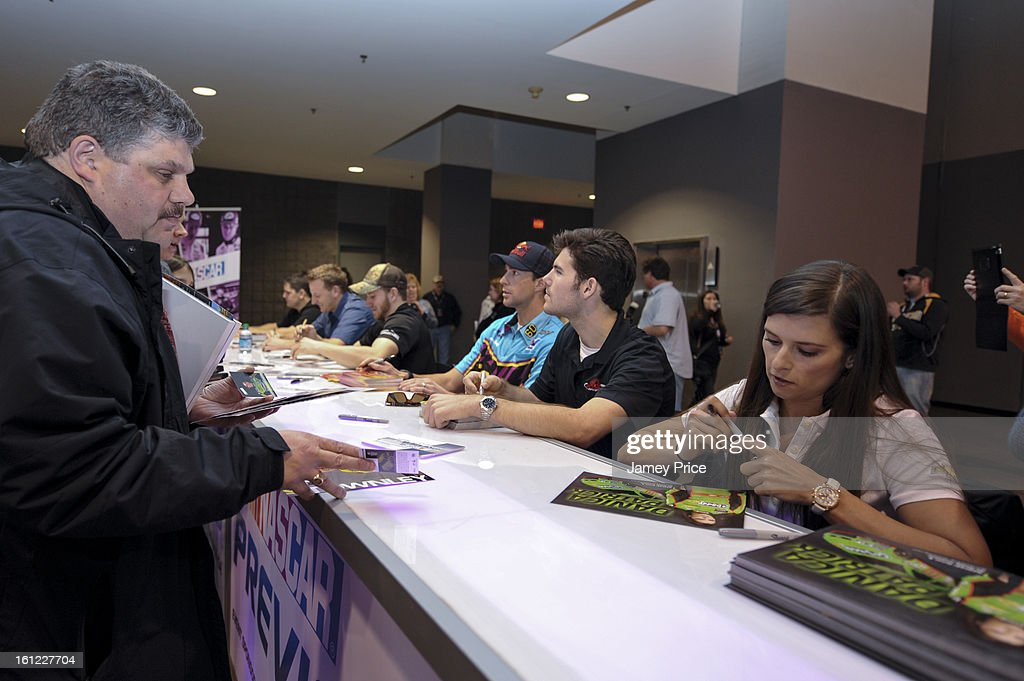 Danica Patrick signs autographs on Saturday afternoon at the NASCAR Hall of Fame on February 9, 2013 in Charlotte, North Carolina.