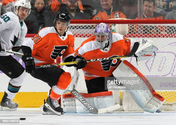 Danick Martel and Michal Neuvirth of the Philadelphia Flyers keep their eye on the loose puck against Chris Tierney of the San Jose Sharks on...