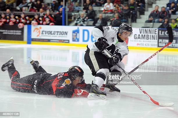 Danick Martel of the BlainvilleBoisbriand Armada moves the puck past a diving Matthieu Desautels of the Baie Comeau Drakkar during the QMJHL game at...