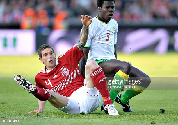 Daniel Agger of Denmark clashes with Mame Diouf of Senegal during their friendly football match on May 27 in Aalborg nothern Denmark ahead of the...