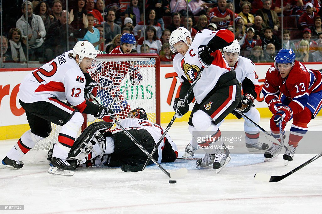 Daniel Alfredsson and Mike Fisher of the Ottawa Senators try to clear the puck from in front of Pascal Leclaire during the NHL game against the...