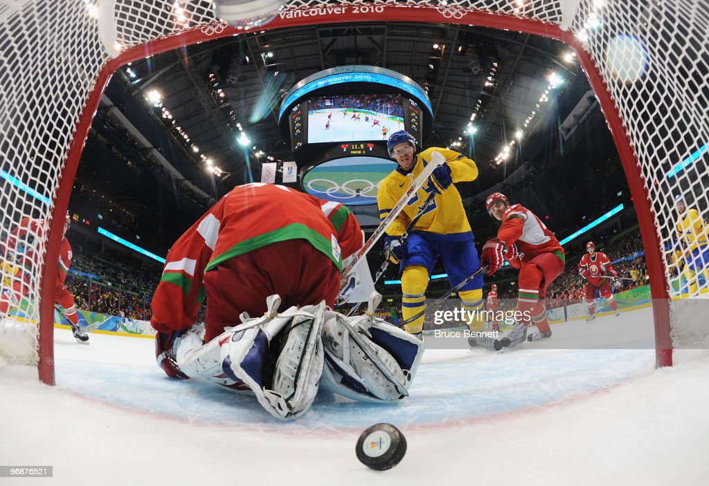 Daniel Alfredsson of Sweden scores a goal past goalkeeper Andrei Mezin of Belarus during the ice hockey men's preliminary game on day 8 of the...