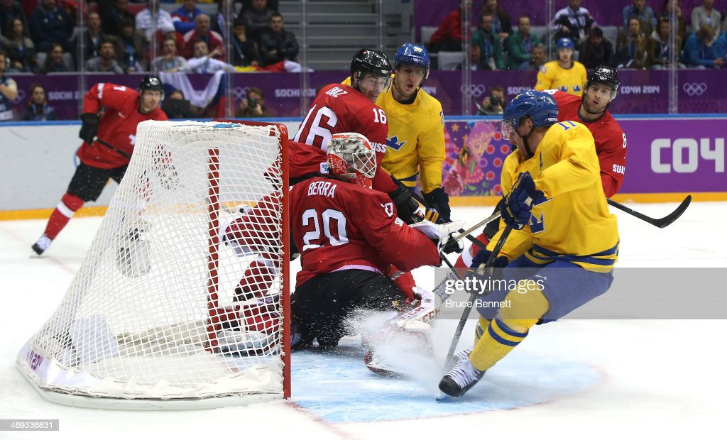 Daniel Alfredsson #11 of Sweden shoots and scores against Reto Berra #20 of Switzerland in the third period during the Men's Ice Hockey Preliminary Round Group C game on day seven of the Sochi 2014 Winter Olympics at Bolshoy Ice Dome on February 14, 2014 in Sochi, Russia.