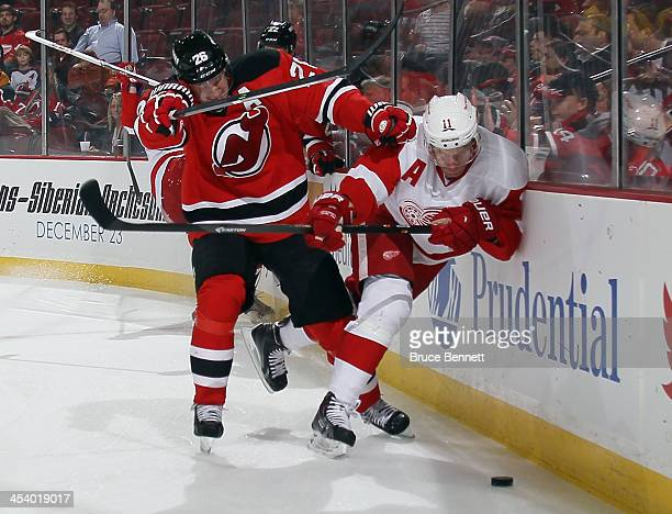 Daniel Alfredsson of the Detroit Red Wings is hit into the boards by Patrik Elias of the New Jersey Devils during the first period at the Prudential...