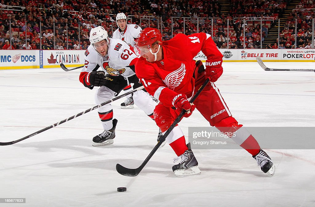 <a gi-track='captionPersonalityLinkClicked' href=/galleries/search?phrase=Daniel+Alfredsson&family=editorial&specificpeople=201853 ng-click='$event.stopPropagation()'>Daniel Alfredsson</a> #11 of the Detroit Red Wings tries to get around the stick of <a gi-track='captionPersonalityLinkClicked' href=/galleries/search?phrase=Eric+Gryba&family=editorial&specificpeople=570539 ng-click='$event.stopPropagation()'>Eric Gryba</a> #62 of the Ottawa Senators during the second period at Joe Louis Arena on October 23, 2013 in Detroit, Michigan.