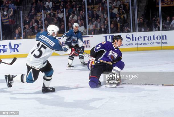 Daniel Alfredsson of the Eastern Conference and the Ottawa Senators shoots as Al MacInnis of the Western Conference and the St Louis Blues tries to...