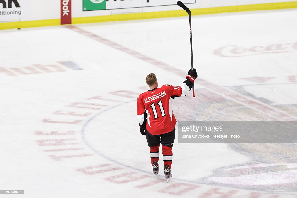 Daniel Alfredsson of the Ottawa Senators acknowledges the fans during warmups on the day he signed a one day contract and then announced his...