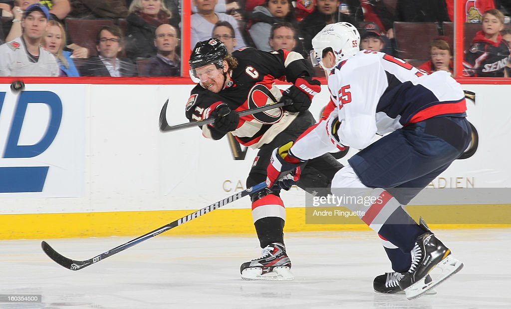 Daniel Alfredsson #11 of the Ottawa Senators has his slapshot deflected off the stick of Jeff Schultz #55 of the Washington Capitals on January 29, 2013 at Scotiabank Place in Ottawa, Ontario, Canada.