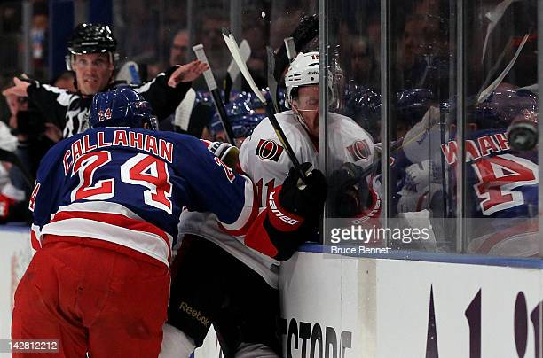 Daniel Alfredsson of the Ottawa Senators is checked into the boards along the bench in the first period by Ryan Callahan of the New York Rangers in...