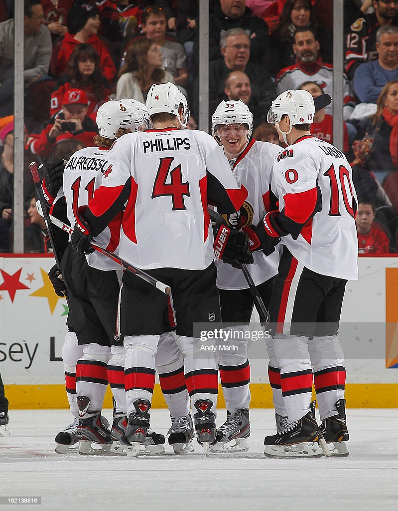 Daniel Alfredsson #11 (L) of the Ottawa Senators is congratulated by his teammates after scoring the game tying goal in the third period against the New Jersey Devils during the game at the Prudential Center on February 18, 2013 in Newark, New Jersey.