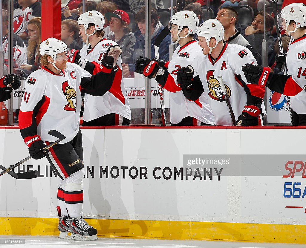 Daniel Alfredsson #11 of the Ottawa Senators is congratulated by his teammates after scoring the game tying goal in the third period against the New Jersey Devils during the game at the Prudential Center on February 18, 2013 in Newark, New Jersey.