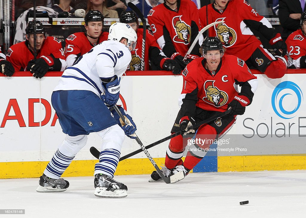 Daniel Alfredsson #11 of the Ottawa Senators makes a pass past a defending Dion Phaneuf #3 of the Toronto Maple Leafs, during an NHL game at Scotiabank Place on February 23, 2013 in Ottawa, Ontario, Canada.
