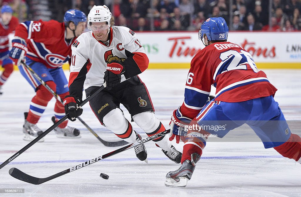 <a gi-track='captionPersonalityLinkClicked' href=/galleries/search?phrase=Daniel+Alfredsson&family=editorial&specificpeople=201853 ng-click='$event.stopPropagation()'>Daniel Alfredsson</a> #11 of the Ottawa Senators moves the puck against defenseman <a gi-track='captionPersonalityLinkClicked' href=/galleries/search?phrase=Josh+Gorges&family=editorial&specificpeople=550446 ng-click='$event.stopPropagation()'>Josh Gorges</a> #26 of the Montreal Canadiens during the NHL game on March 13, 2013 at the Bell Centre in Montreal, Quebec, Canada.