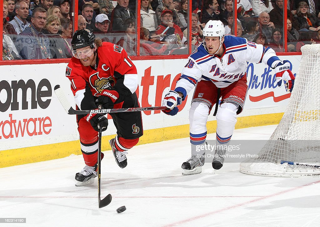 Daniel Alfredsson #11 of the Ottawa Senators passes the puck as Marc Staal #18 of the New York Rangers uses his stick to slow him down, during an NHL game at Scotiabank Place on February 21, 2013 in Ottawa, Ontario, Canada.
