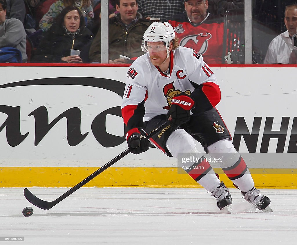 Daniel Alfredsson #11 of the Ottawa Senators plays the puck against the New Jersey Devils during the game at the Prudential Center on February 18, 2013 in Newark, New Jersey.