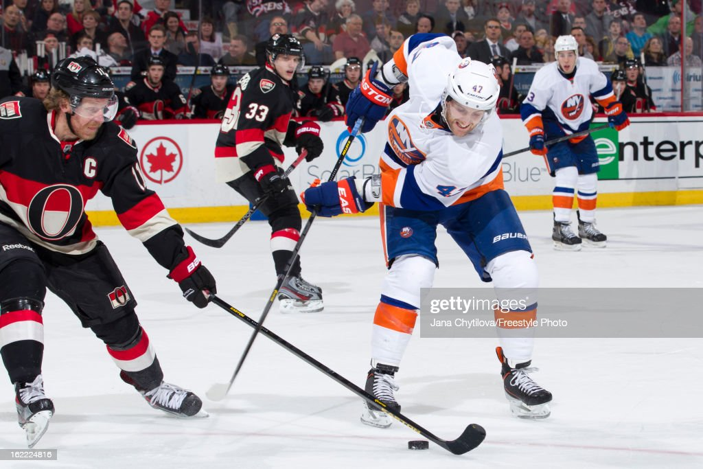 Daniel Alfredsson #11 of the Ottawa Senators poke checks the puck away from Andrew MacDonald #47 of the New York Islanders during an NHL game at Scotiabank Place on February 19, 2013 in Ottawa, Ontario, Canada.