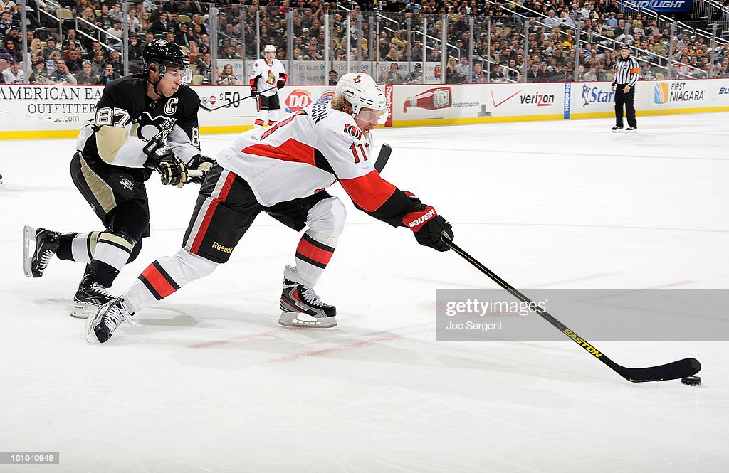 Daniel Alfredsson #11 of the Ottawa Senators reaches for the loose puck in front of Sidney Crosby #87 of the Pittsburgh Penguins on February 13, 2013 at Consol Energy Center in Pittsburgh, Pennsylvania.