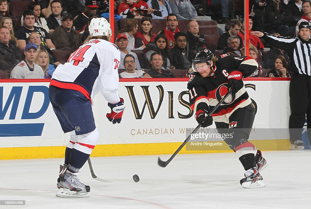 Daniel Alfredsson #11 of the Ottawa Senators shoots the puck against John Carlson #74 of the Washington Capitals on January 29, 2013 at Scotiabank Place in Ottawa, Ontario, Canada.