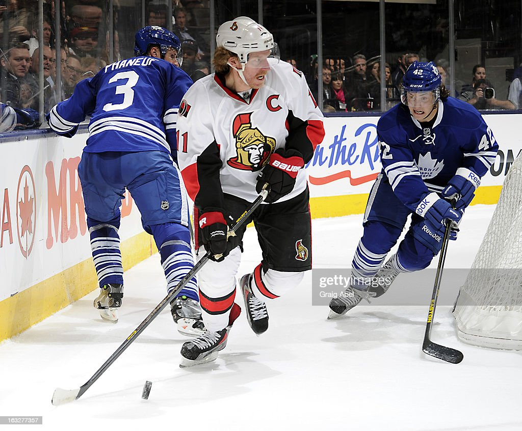 Daniel Alfredsson #11 of the Ottawa Senators skates the puck away from Dion Phaneuf #3 and Tyler Bozak #42 of the Toronto Maple Leafs during NHL game action March 6, 2013 at the Air Canada Centre in Toronto, Ontario, Canada.