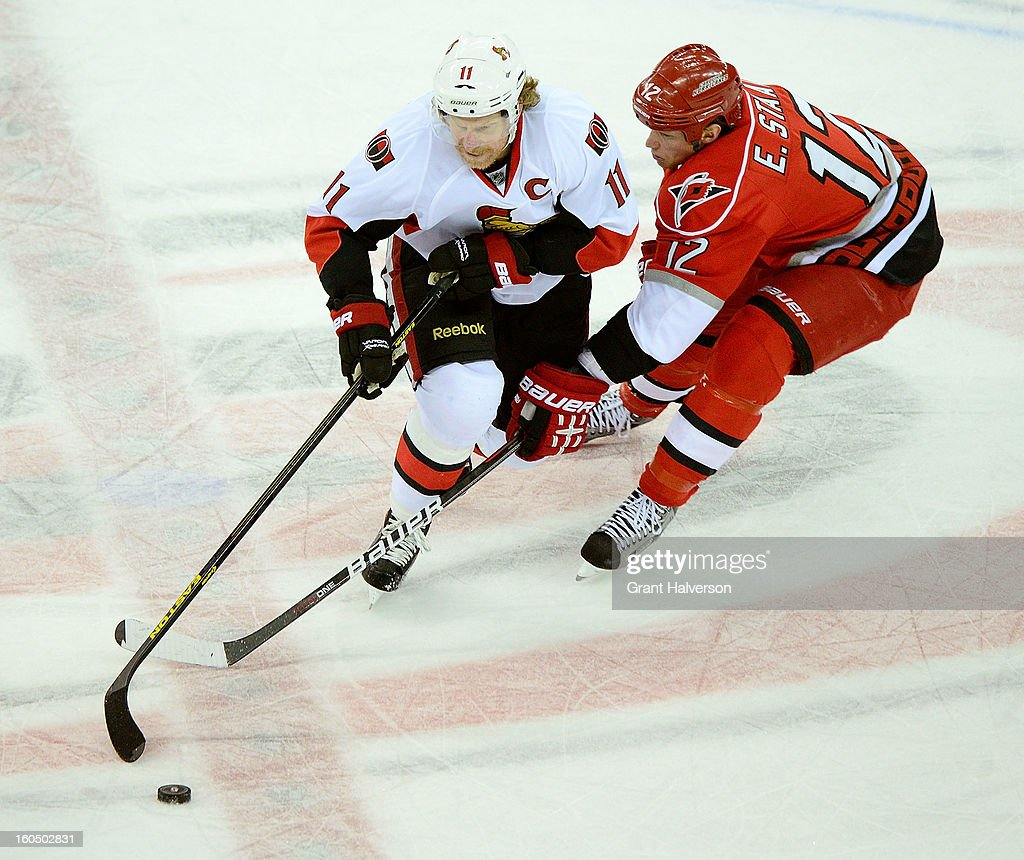 Daniel Alfredsson #11 of the Ottowa Senators moves the puck against Eric Staal #12 of the Carolina Hurricanes during play at PNC Arena on February 1, 2013 in Raleigh, North Carolina. The Hurricanes defeated the Senators 1-0.