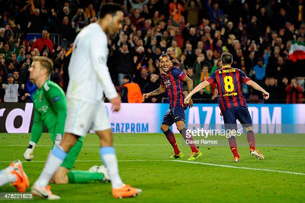 Daniel Alves of Barcelona celebrates with teammate Andres Iniesta after scoring his team's second goal during the UEFA Champions League Round of 16...