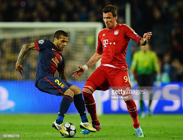 Daniel Alves of Barcelona is challenged by Mario Mandzukic of Munich during the UEFA Champions League semi final second leg match between Barcelona...