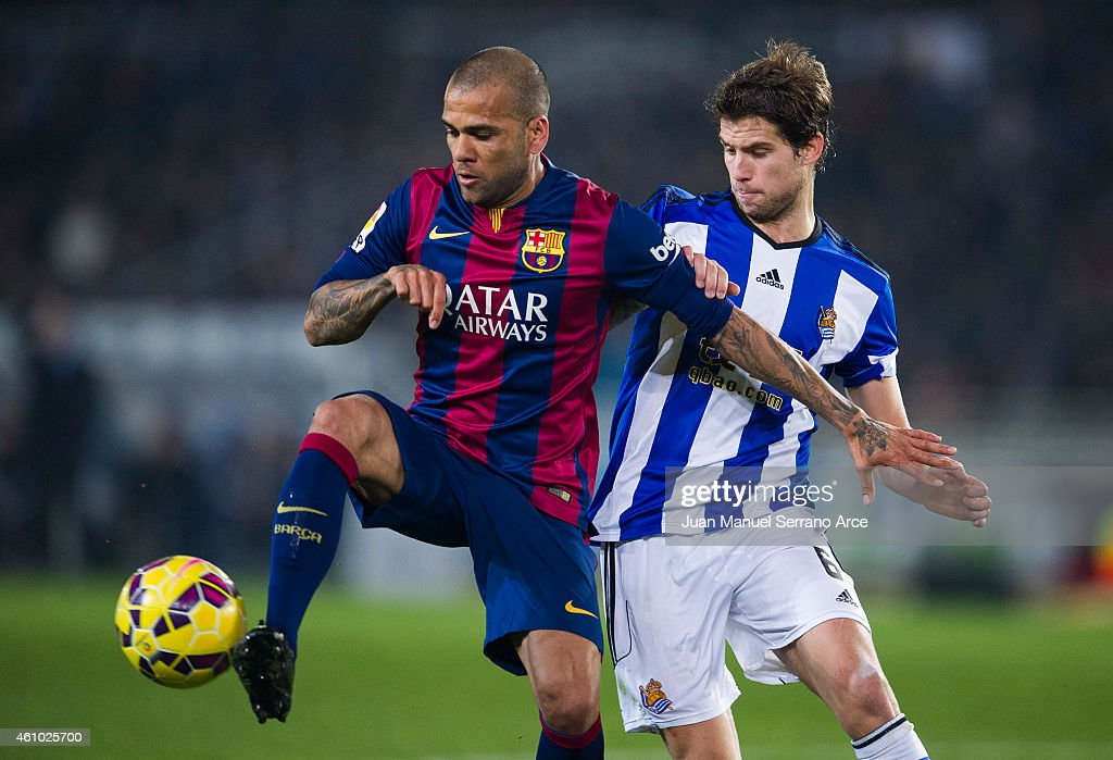 Daniel Alves of FC Barcelona duels for the ball with Inigo Martinez of Real Sociedad during the La Liga match between Real Sociedad and Barcelona at...