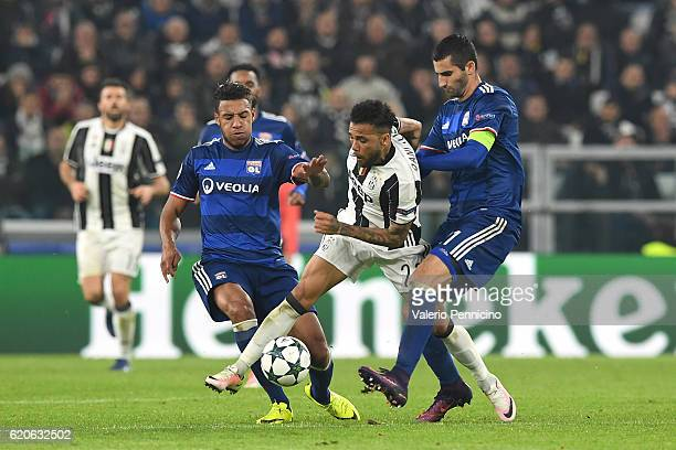 Daniel Alves of Juventus is challenged by Maxime Gonalons and Corentin Tolisso of Olympique Lyonnais during the UEFA Champions League Group H match...