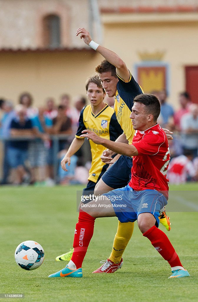 Daniel Aquino Pintos (2nd L) of Atletico de Madrid competes for the ball with Luis Valcarce (R) of Numancia CD during the Jesus Gil y Gil Trophy between Club Atletico de Madrid and Numancia C. D. at Sporting Club Uxama on July 21, 2013 in Burgo de Osma, Soria, Spain.