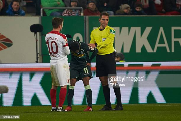 Daniel Baier of Augsburg and Referee Tobias Stieler and Raffael of Moenchengladbach looks on during the Bundesliga match between FC Augsburg and...