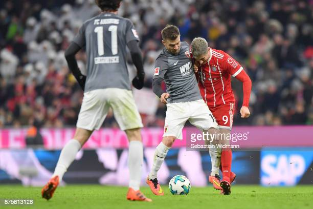 Daniel Baier of Augsburg and Robert Lewandowski of FC Bayern Muenchen compete for the ball during the Bundesliga match between FC Bayern Muenchen and...