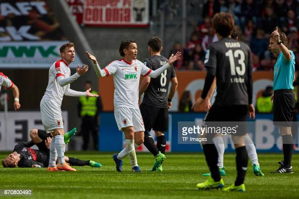 Daniel Baier of Augsburg and Usami Takashi of Augsburg gestures during the Bundesliga match between FC Augsburg and 1 FC Koeln at WWK Arena on April...