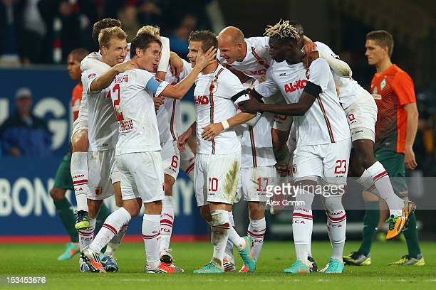 Daniel Baier of Augsburg celebrates his team's third goal with team mates during the Bundesliga match between FC Augsburg and SV Werder Bremen at SGL...