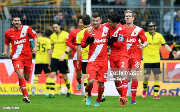 Daniel Baier of Augsburg celebrates with team mates after scoring his teams first goal during the Bundesliga match between Borussia Dortmund and FC...