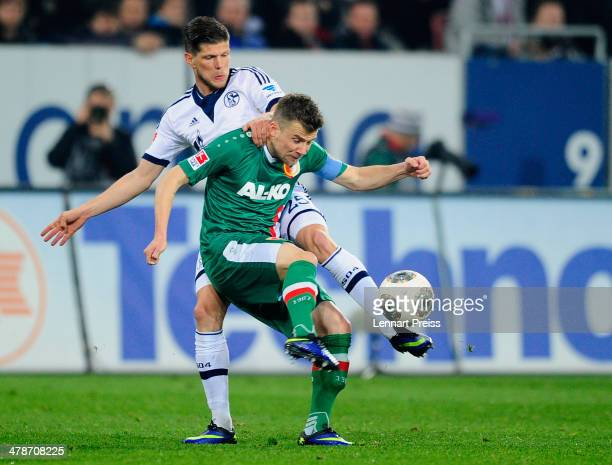 Daniel Baier of Augsburg challenges KlaasJan Huntelaar of Schalke during the Bundesliga match between FC Augsburg and FC Schalke 04 at SGL Arena on...