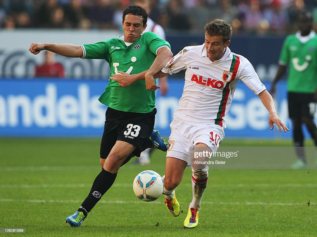 Daniel Baier (R) of Augsburg fights for the ball with Manuel Schmiedebach of Hannover during the Bundesliga match between FC Augsburg and Hannover 96 at SGL Arena on September 24, 2011 in Augsburg, Germany.