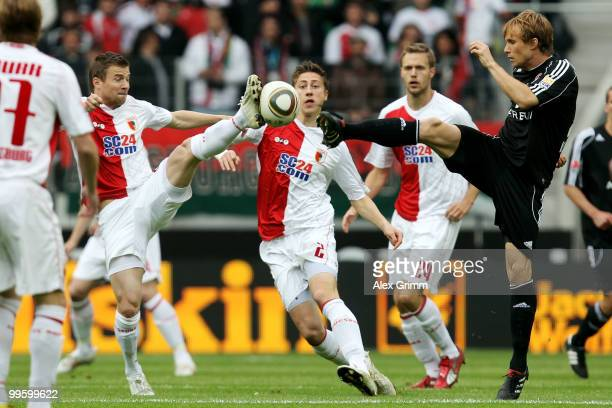 Daniel Baier of Augsburg is challenged by Andreas Ottl of Nuernberg during the Bundesliga play off leg two match between FC Augsburg and 1 FC...