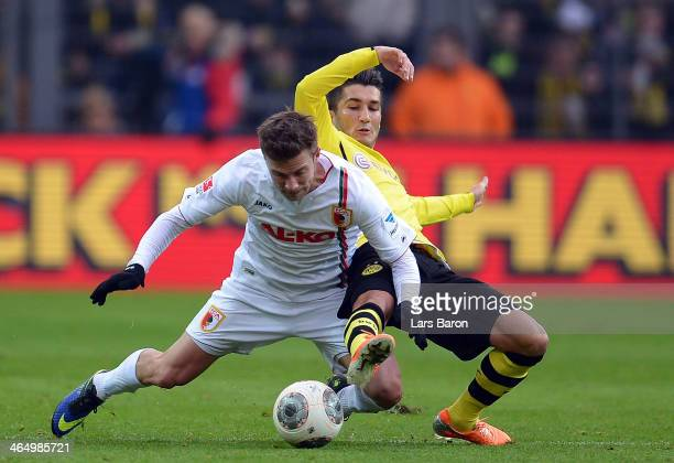 Daniel Baier of Augsburg is challenged by Nuri Sahin of Dortmund during the Bundesliga match between Borussia Dortmund and FC Augsburg at Signal...