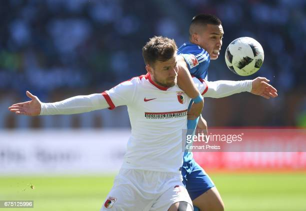 Daniel Baier of FC Augsburg challenges Bobby Wood of Hamburger SV during the Bundesliga match between FC Augsburg and Hamburger SV at WWK Arena on...